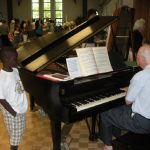 man playing piano while child watches